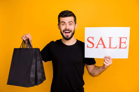 Photo of crazy millennial guy holding shopping packs offer low prices shopping showing paper card with sale announce wear black t-shirt isolated yellow color background