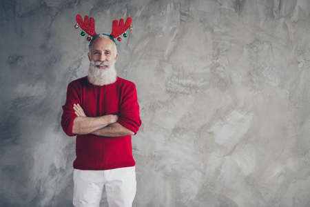 Portrait of modern trendy old man in red deer horns headband cross hands enjoy x-mas party christmas time celebration wear stylish jumper white pants isolated grey concrete wall color background