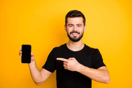 Positive cool guy promoter hold cellphone touchscreen point index finger recommend modern technology suggest select black friday wear good looking outfit isolated vivid color background