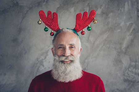 Portrait of positive stylish old man hipster in deer headband enjoy christmas party x-mas celebration wear red modern pullover isolated over grey concrete wall color background Stok Fotoğraf