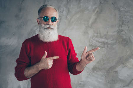 Portrait of harsh masculine cool old man point index finger copyspace recommend x-mas tradition discounts wear red jumper isolated over grey concrete wall color background Banco de Imagens