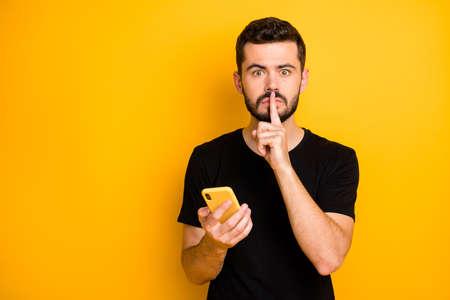Censuur geen geheim concept. Ernstige kerel blogger hold gebruik mobiel zoeken privé nep nieuws show mute stil teken wijsvinger draag zwart t-shirt geïsoleerd gele kleur achtergrond Stockfoto