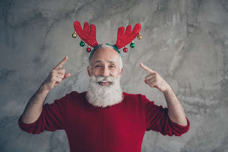 Portrait of funky grey white hair old man wearing red deer horns point index finger enjoy christmas x-mas party masquerade wear stylish sweater isolated over grey color background