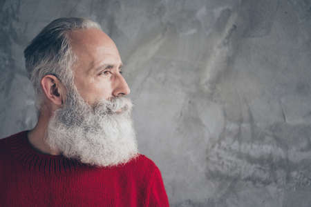 Closeup photo of nice aged guy looking side empty space minded wear red knitted pullover jumper cool hipster santa outfit isolated grey color concrete wall background 版權商用圖片