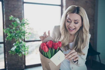 Photo of beautiful blond business lady came workplace looking fresh tulips bunch little postcard on table interested who is addresser read card modern office
