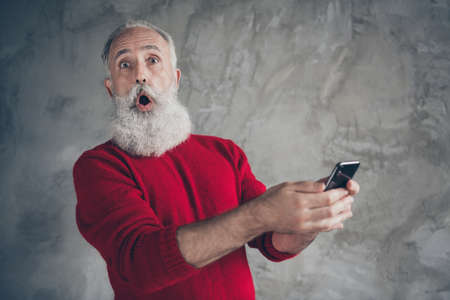 Funny funky crazy white hair beard old man use his smartphone blogging get x-mas newyear season tradition discounts notification wear red jumper isolated over grey color background