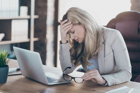 Photo of amazing blond business lady holding head on hand tired feel dizzy overwhelmed assistant notebook table sitting chair formalwear blazer modern office Reklamní fotografie