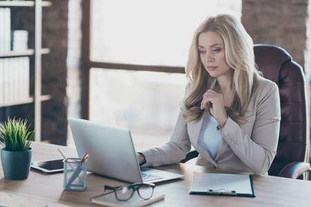 Photo d'une femme d'affaires blonde étonnante personne ingénieuse à la recherche d'un ordinateur portable sérieux sur une table assise sur une chaise de patron blazer dans un bureau moderne Banque d'images