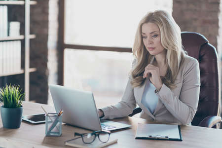 Photo of amazing blond business lady resourceful person looking seriously notebook on table sitting boss chair formalwear blazer in modern office Imagens