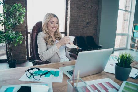 Photo of beautiful blond business lady looking notebook table holding coffee beverage speaking skype partners break sitting chair formalwear blazer in modern office