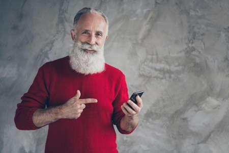 Regardez les réductions de Noël. Heureux vieil homme moderne utiliser un téléphone intelligent recevoir une notification salutations de tradition du nouvel an direct porter un cavalier rouge isolé sur fond de couleur de mur de béton gris Banque d'images