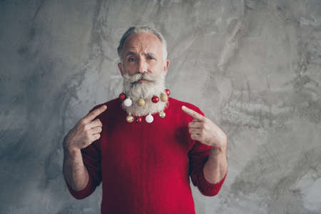 Portrait of serious masculine cool old man point index finger on christmas tree toy hang on his beard x-mas party wear red jumper isolated grey concrete wall color background Banco de Imagens