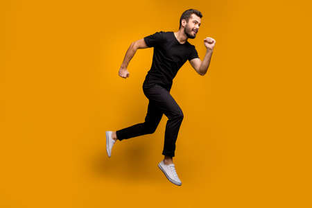 Full size photo of handsome millennial guy jumping high rush shopping mall black friday offers season fast wear black t-shirt trousers isolated yellow color background