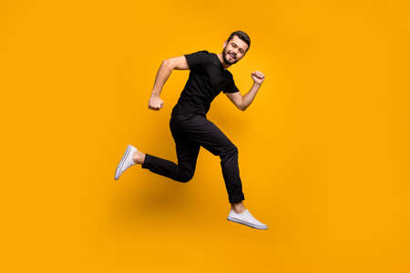 Full body profile photo of handsome millennial guy jumping high rushing shopping mall best black friday offers season wear black t-shirt trousers isolated yellow color background Zdjęcie Seryjne