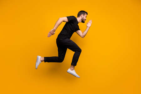Full body profile photo of handsome millennial guy jumping high rushing low prices discount shopping mall wear black t-shirt trousers isolated yellow color background