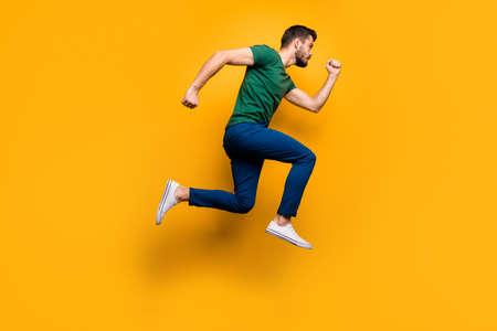 Photo de profil pleine longueur d'un gars sérieux et concentré qui saute vite veut acheter des rabais de vendredi noir de printemps portent une tenue de style décontracté isolée sur fond de couleur jaune