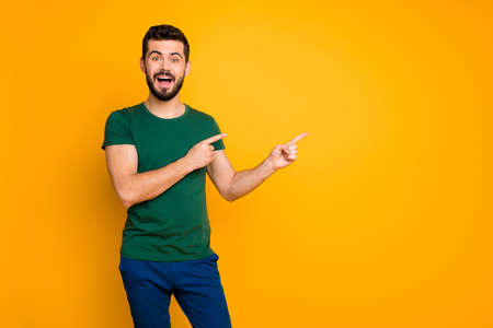 Portrait of excited crazy guy promoter look incredible discounts information scream wow omg indicate adverts promo point index finger copyspace wear blue pants isolated yellow color background