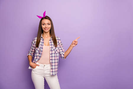 Portrait of positive cheerful cool girl promoter point index finger copyspace enjoy adverts recommend promotion wear retro pin-up white pants trousers isolated over violet color background