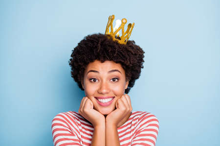 Close up photo of beautiful dark skin wavy lady in best mood cheerfully smiling wear amazing golden crown casual striped sweater isolated blue color background