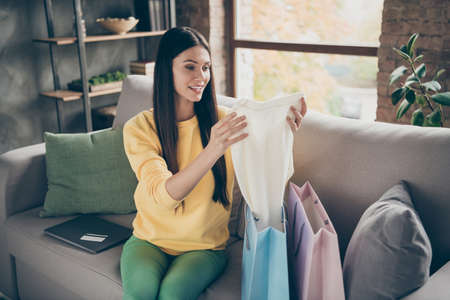 Portrait of positive excited girl get shopping purchase through e-commerce bank card payment hold white new jumper sit cozy couch in home indoors