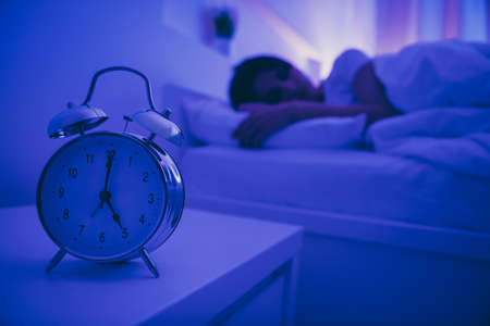 Close-up view of alarm call bell clock nice attractive peaceful serene girl lying in bed covered by soft blanket fallen asleep healthy life regime in dark illuminated room house hotel flat