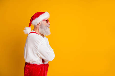 Profile side photo of serious brutal santa claus hipster look funky copyspace cross hands want celebrate christmas fairy newyear time fast isolated yellow color background