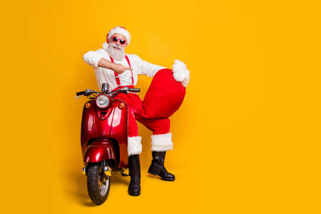 Big christmas wish delivery. Full length photo of funky grandfather in santa claus hat shirt suspenders hold magic sack x-mas party point index finger sit bike isolated yellow color background