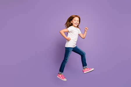 Full body profile photo of funny small foxy lady jumping high rejoicing rushing shopping discounts speed wear casual t-shirt jeans isolated purple background Фото со стока