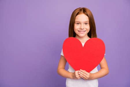 Feliz día de la madre. Foto de bastante pequeña dama astuta sostenga gran figura de corazón de papel rojo saludo madre presente de vacaciones sorpresa vestir camiseta blanca fondo púrpura aislado