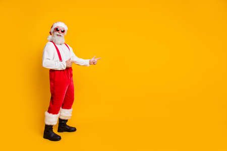 Full size photo of funky funny grey bearded santa claus in red hat point index finger copyspace indicate x-mas noel discounts newyear resolution isolated yellow color background