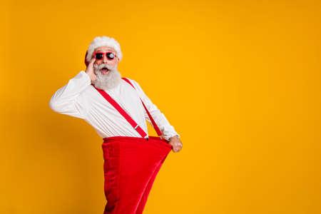 Profiel kant foto van gekke funky witte baard haar kerstman in hoed houden groot formaat broek afvallen x-mas vieren noel dieet effect schreeuw geïsoleerde gele kleur achtergrond