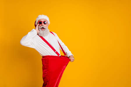 Profile side photo of crazy funky white beard hair santa claus in hat hold big size pants lose weight x-mas celebrate noel diet effect scream isolated yellow color background
