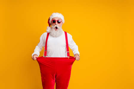 Portret van gekke funky wit bebaarde grootvader in Kerstman hoed houden grote broeken afvallen buik x-mas tijd show dieet effect geïsoleerde gele kleur achtergrond