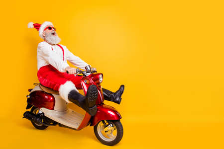 Full body photo of crazy santa white hair grandpa rushing x-mas party speed by retro bike wear trendy sun specs red trousers cap shirt boots isolated yellow color background Banco de Imagens