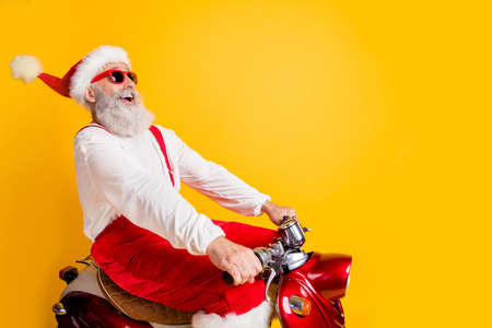 Profile photo of stylish santa white hair grandpa rushing x-mas theme party by retro bike wear trendy sun specs red trousers cap shirt isolated yellow color background