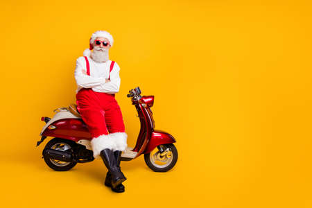 Full body photo of self-confident santa man festive mood ready x-mas theme party sitting retro bike wear sun specs pants cap shirt boots isolated yellow color background