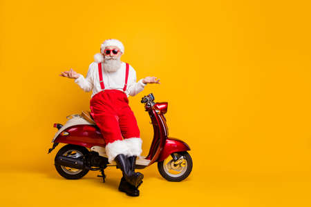Full size photo of santa sit moped shrug shoulders not feel guilty coming party without gift wear specs suspenders pants cap shirt boots isolated yellow color background