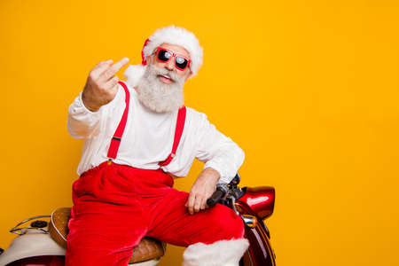 Photo of crazy white grey hair santa sitting on bike showing impolite gesture careless mood bad person wear sun specs pants cap shirt isolated yellow color background