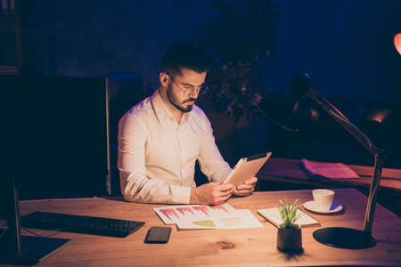 Workaholic stay evening office concept. Focused marketer work on his modern tablet search information about company enterprise development sit table in dark loft company