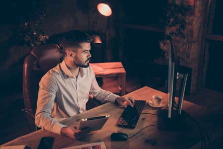 Top above angle view photo of serious pensive man bearded holding tablet and calculating on pc comparing data saved on both electronic devices