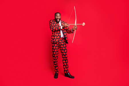 Full body photo of funny dark skin man with bow and love arrow amour cupid role see good couple wear hearts pattern suit shirt necktie tie boots outfit isolated red color background 免版税图像 - 134370269