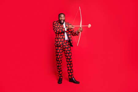 Photo complète du corps d'un homme drôle à la peau foncée avec un arc et une flèche d'amour rôle de cupidon voir un bon couple porter des coeurs motif costume chemise cravate cravate bottes tenue isolé fond de couleur rouge