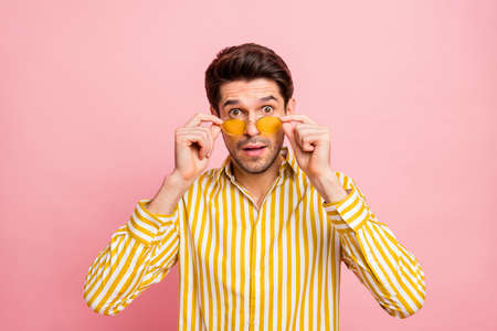 Photo of handsome macho guy looking stupor taking eyeglasses off not believe eyes low prices wear sun specs stylish striped shirt isolated pink color background Stockfoto