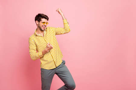 Photo of handsome macho guy celebrating cool victory raising fists yelling gladly wear sun specs stylish striped shirt pants isolated pink pastel color background