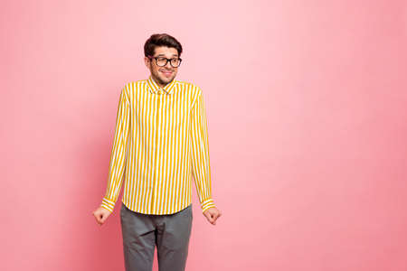 Photo of amazing guy looking side empty space avoiding eyes shy person listen compliments wear specs stylish striped shirt trousers isolated pink color background