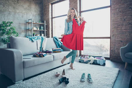 Full length body size view of nice attractive charming pretty fashionable cheerful cheery wavy-haired girl trying red dress preparing wardrobe for voyage at modern industrial loft brick style interior Standard-Bild
