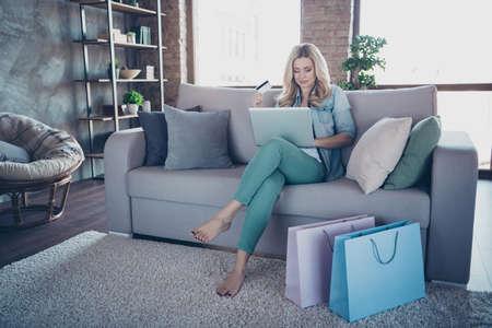 Portret van haar aardige, charmante, mooie dame met golvend haar zittend op een divan met behulp van een laptop die online bestellingen doet, spullen koopt en internationale bezorging koopt in een industriële loft-stijl binnenkamer