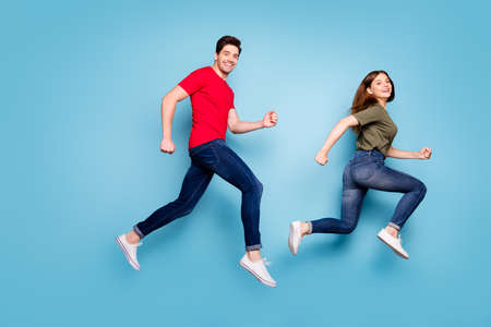 Full size profile side photo of cheerful romantic married people jump run after spring discounts wear green red t-shirt denim jeans sneakers isolated over blue color background