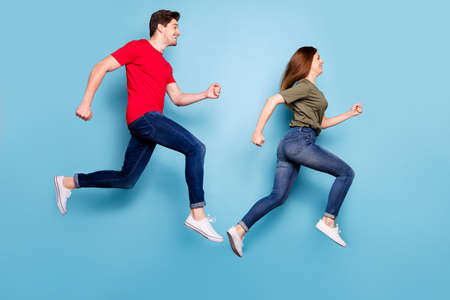 Full body profile side photo of cheerful excited couple jump run hurry for summer sales wear green red t-shirt denim jeans sneakers isolated over blue color background Stockfoto