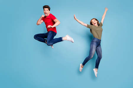Full size photo of funky crazy two people spouses students man fight kick hands fists woman jump fool raise arms wear green red t-shirt denim jeans sneakers isolated blue color background Stockfoto - 134370579